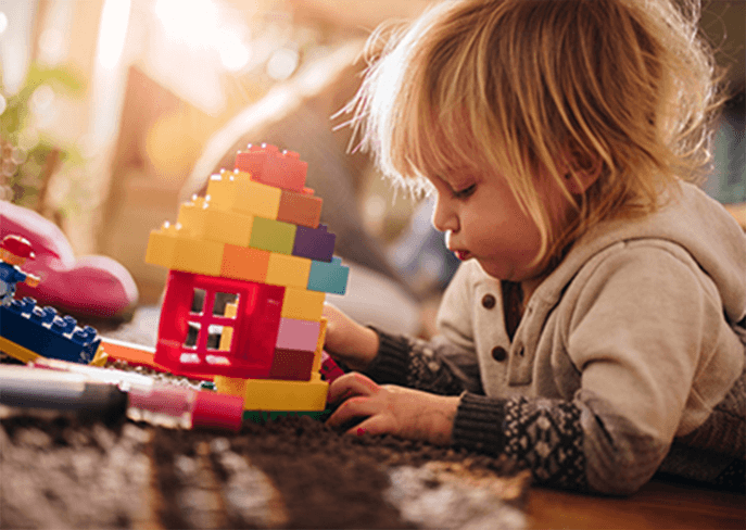 Toddler playing with toy bricks